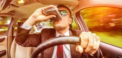 Мужчина за рулем с выпивкой