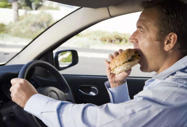 Мужчина за рулем ест гамбургер